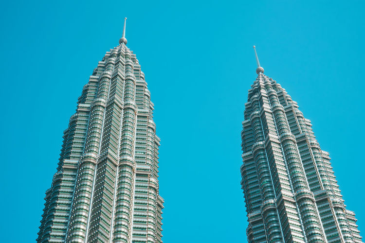 Low angle view of petronas towers against clear blue sky