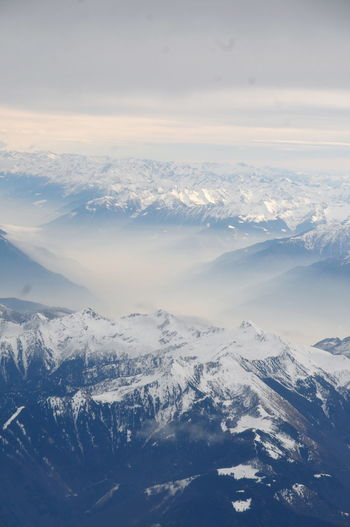 Aerial view of snowcapped mountains against sky during winter