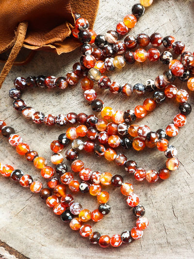 Sunny beads of amber fireplace faceted agate with leather jewelry pouch bag on rustic background High Angle View No People Orange Color Fruit Freshness Still Life Indoors  Directly Above Large Group Of Objects Celebration Close-up Table Bead Red Necklace Day Orange Sunny Beads Faceted Crystal Ball Agate Leather Bag Jewelry Pouch Rustic Style