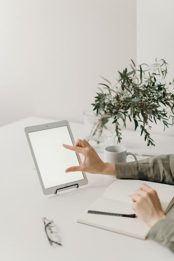 Cropped hand of woman using digital tablet at office