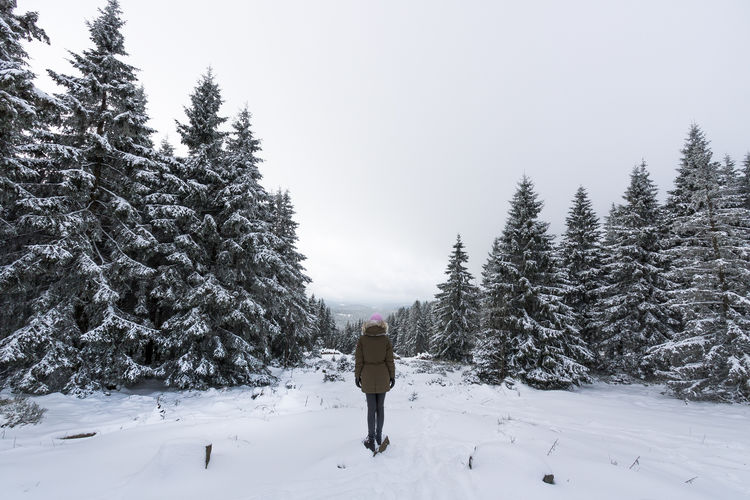 Rear view of woman walking on snow covered field