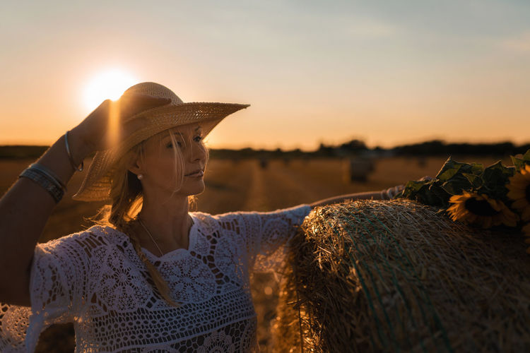 Portrait of woman wearing straw hat standing against sky during sunset