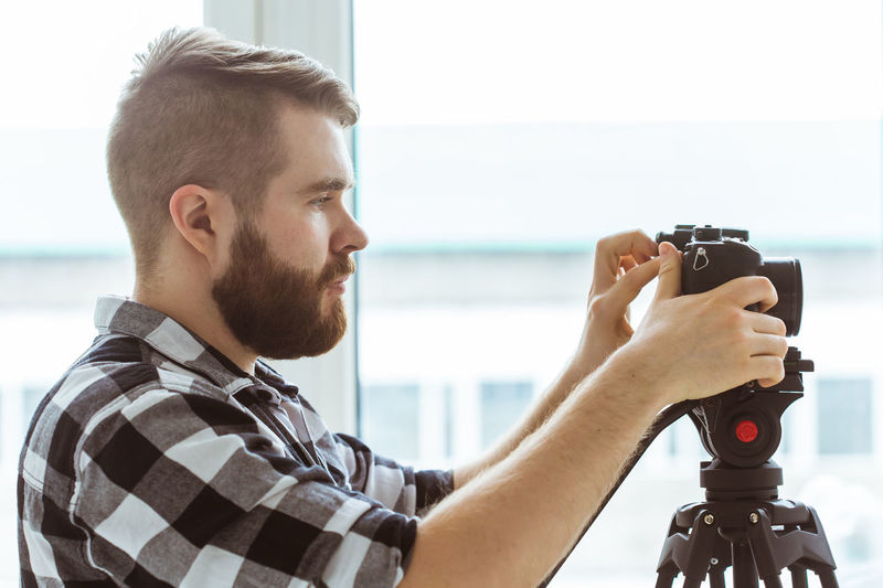 Profile view of man holding camera indoors