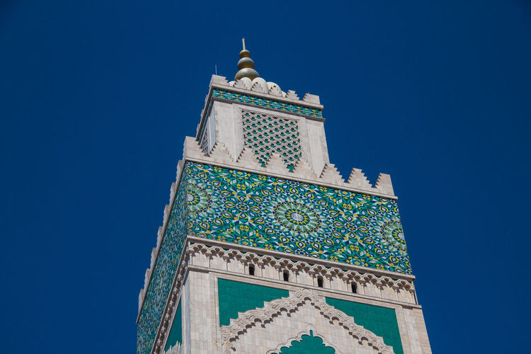 Low angle view of hassan ii mosque tower against blue sky - casablanca, morocco
