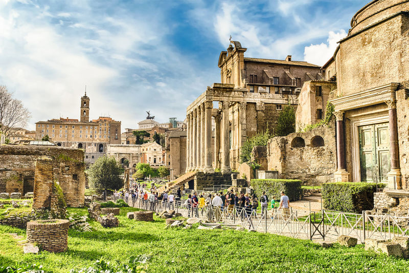 Tourist walking by old ruins at roman forum against sky