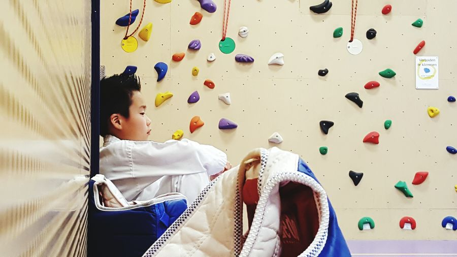 Side View Of Boy Sitting Against Artificial Climbing Wall