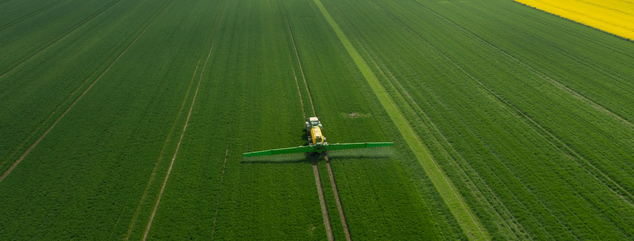 Tractor with field sprayer when applying pesticide against pesticide