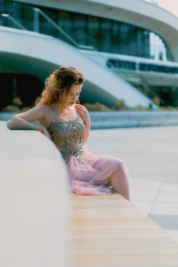 Young woman sitting on bridge