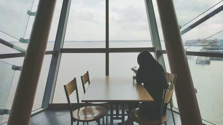 Rear view of woman sitting on chair in restaurant against sea