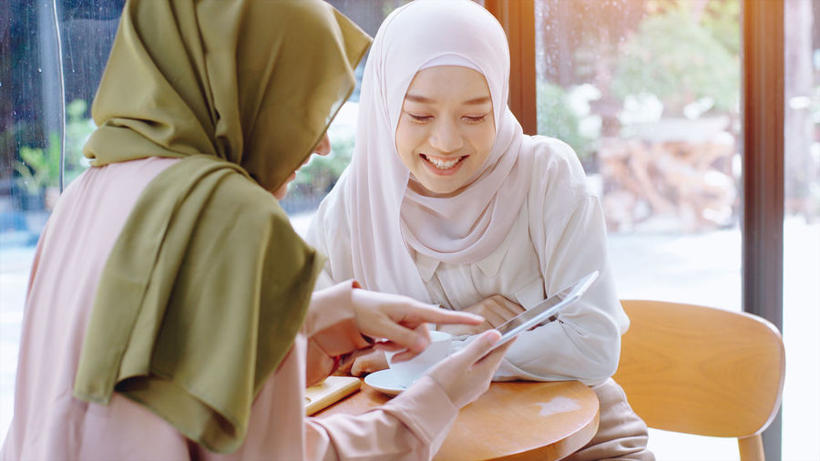 Beautiful young women in hijab looking at mobile phone at cafe