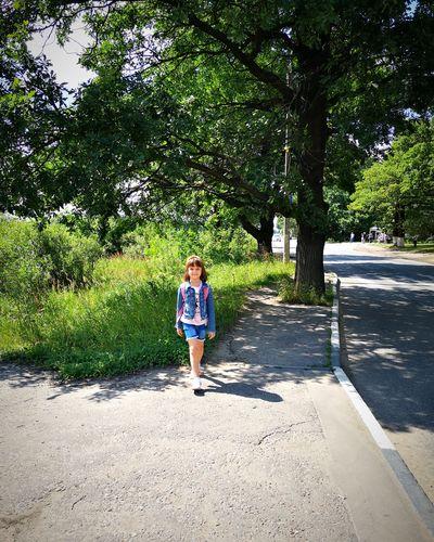 Full length of girl walking on sidewalk during sunny day