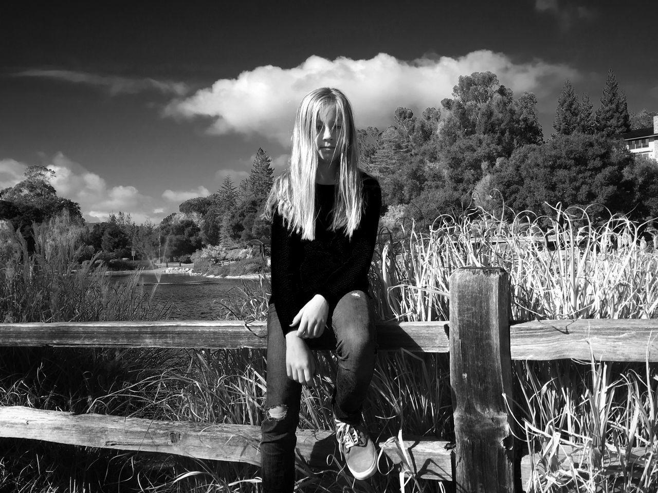 Girl sitting on railing against trees