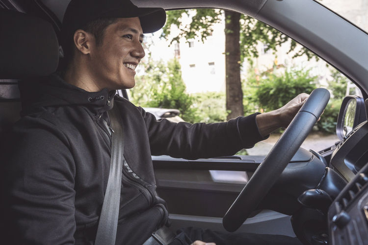 Side view of young man sitting in car