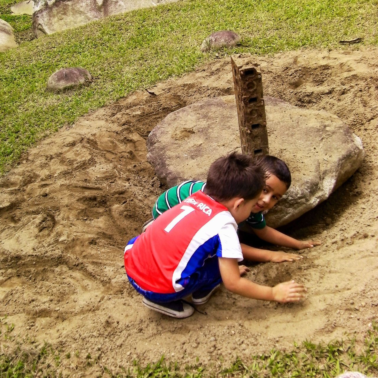 real people, leisure activity, childhood, full length, high angle view, boys, sand, day, outdoors, lifestyles, sitting, elementary age, field, grass, nature, animal themes, mammal, people