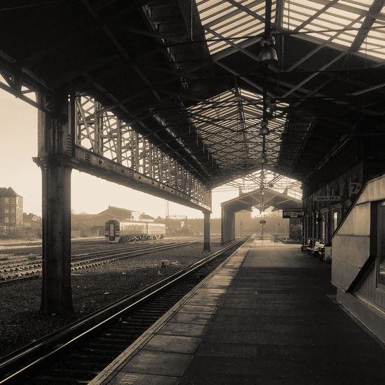 An empty platform in an empty station Architecture Built Structure Day Empty Geometry Lines Monochrome No People Quiet Railway Station Roof Sepia Steelwork Sunny Train Transportation