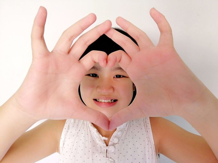 Close-up portrait of smiling girl making heart shape against wall