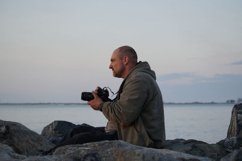 Man photographing on rock by sea against sky