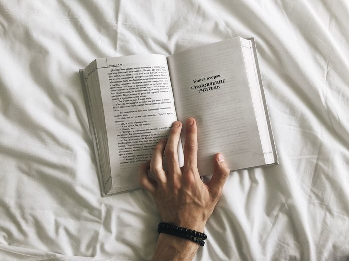 Midsection of man reading book on bed