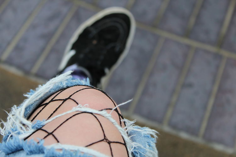 Low section of woman wearing torn jeans and shoes on footpath