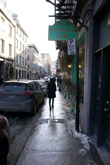 Rear view of people walking on street in city during rainy season