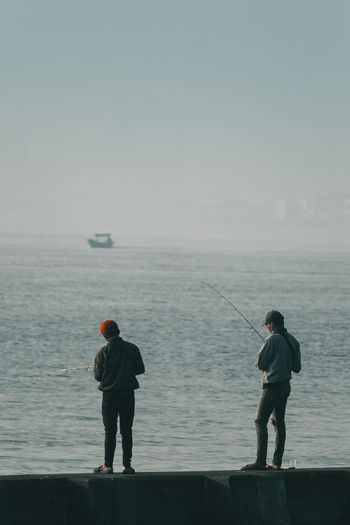 Rear view of men standing by sea against sky while fishing