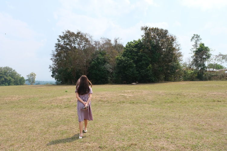 Rear view of woman on field against sky