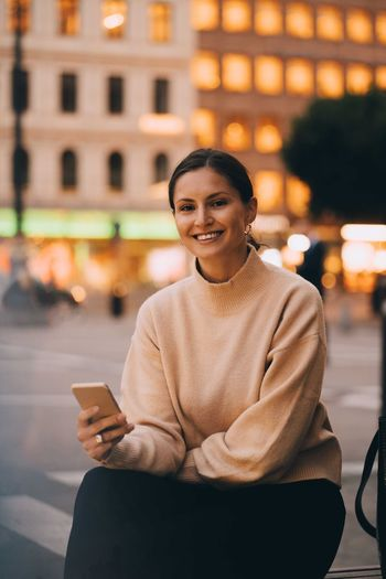 Smiling young man using mobile phone in city
