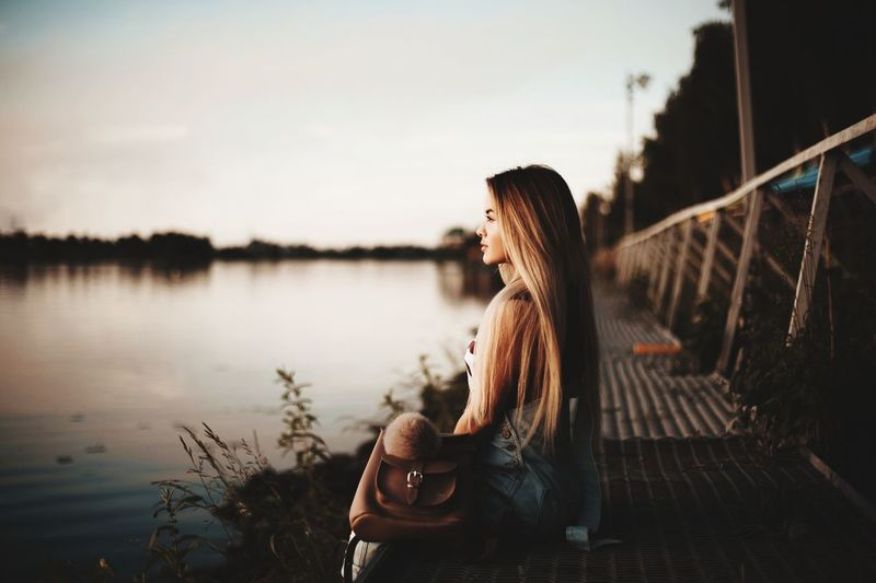 Profile view of thoughtful young woman sitting on boardwalk at lake