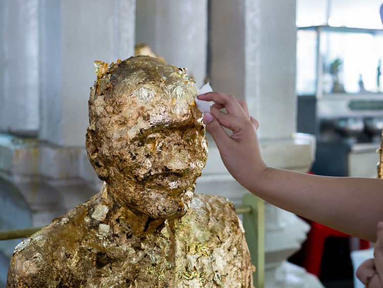 Hand gilding a gold leaf on the Buddha statue. Hand Human Hand One Person Human Body Part Focus On Foreground Holding Real People Lifestyles Women Day Leisure Activity Body Part Gold Leaf Buddha Thailand Statue Gilding Metal Golden Religious  Architecture Decoration Travel Traditional