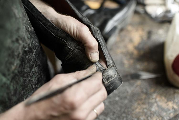 Cropped Image Of Shoemaker Holding Shoe