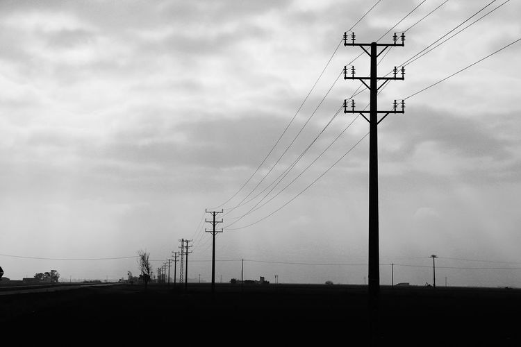 Low angle view of silhouette electricity pylon on field against sky