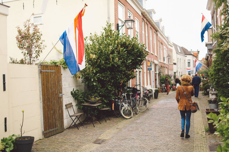 Rear view of woman walking amidst dutch flags on buildings