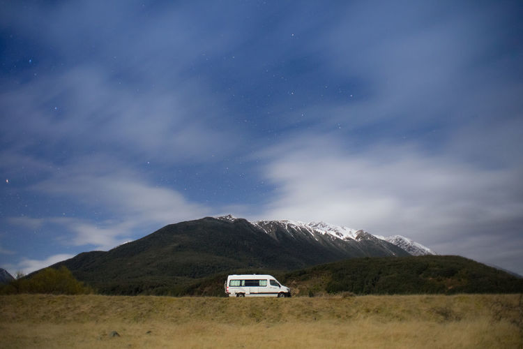 A motorhome park at the campsite in new zealand during night with snowcapped mountain in background.