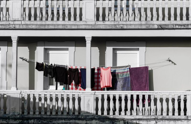 Clothes drying on railing against building in city