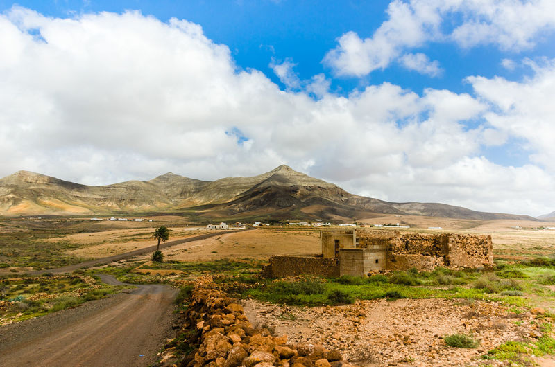 Beauty In Nature Built Structure Cloud Cloud - Sky Cloudy Dirt Road Fuerteventura Grass Landscape Mountain Mountain Range Nature Road Scenics Sky The Way Forward Tranquil Scene Tranquility The KIOMI Collection The Great Outdoors - 2016 EyeEm Awards The Great Outdoors With Adobe