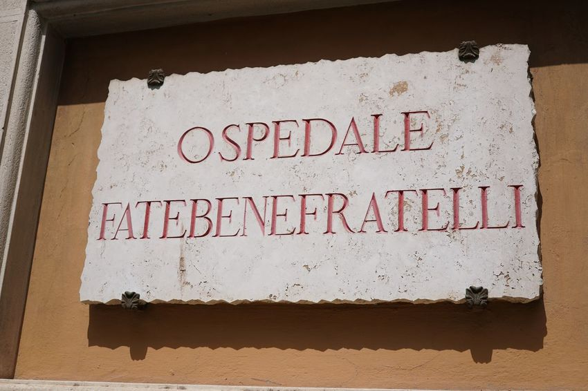 Marble plaque of the Fatebenefratelli Hospital established in 1585 on the western side of the Tiber Island in Rome Hospital Isola Tiberina Isola Tiberina Rome Clinic Close-up Fatebenefratelli Marble Plate No People Ospedale Plaque Script Sign Tiber Island Tiber Island Rome