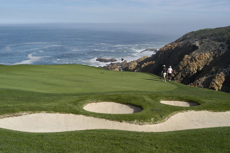Scenic view of golf course by sea against sky