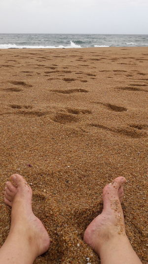 Low section of man legs on sand at beach