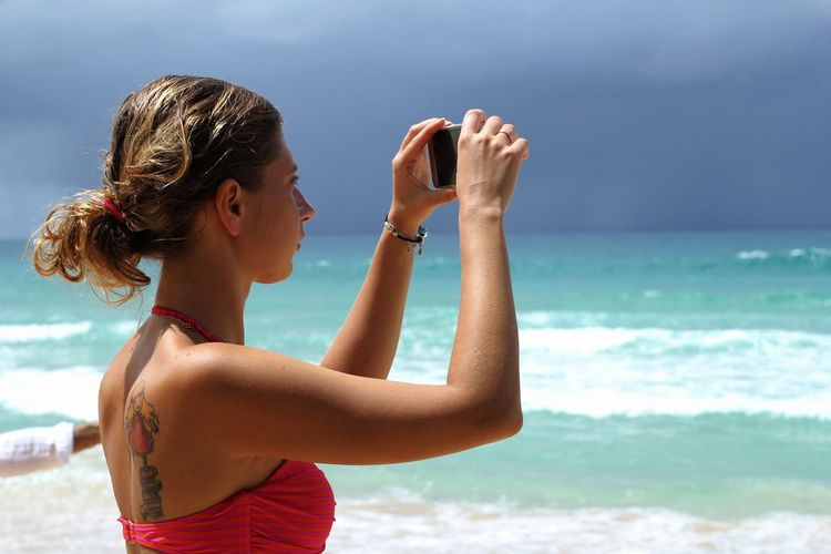 Side view of woman photographing at beach against sky