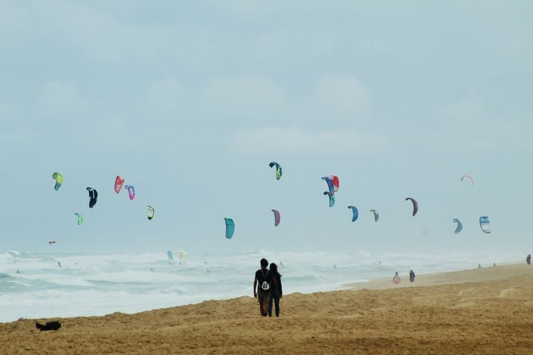 People at beach against sky and parachutes