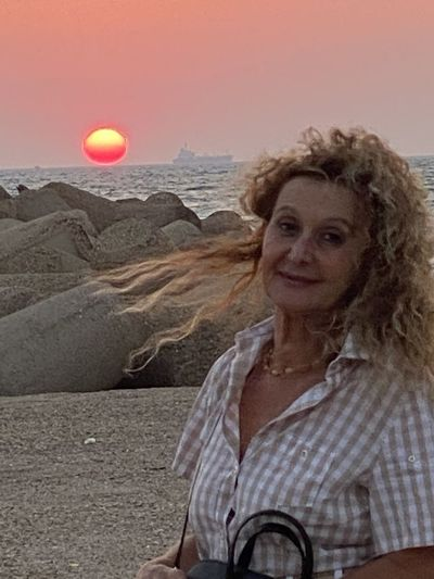 Portrait of a smiling mid adult woman against sunset sky