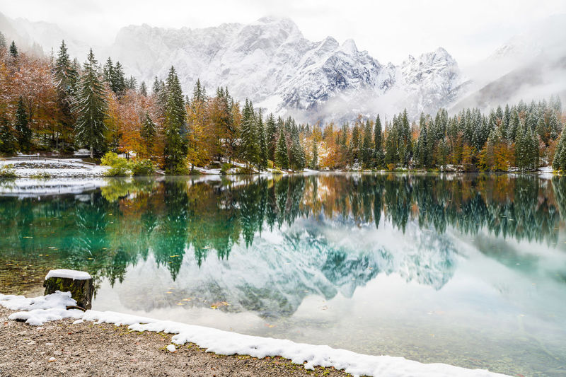 Scenic view of lake by snowcapped mountains during winter