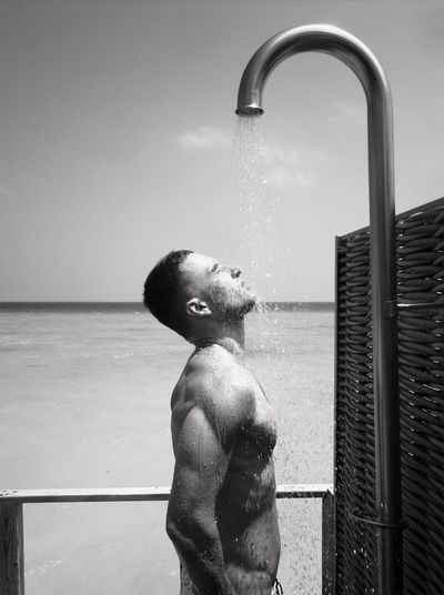 Profile view of shirtless muscular man taking shower at beach