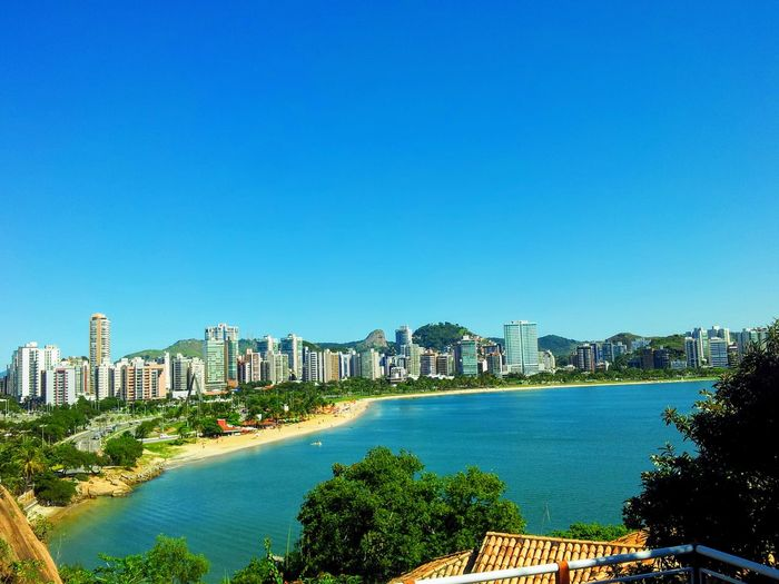 Sea and buildings against clear blue sky