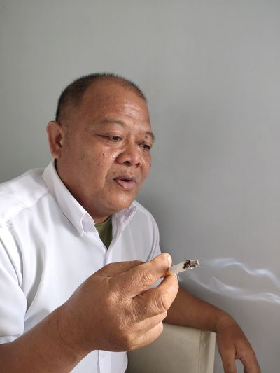 Portrait of indonesian man smoking cigarette against white background.
