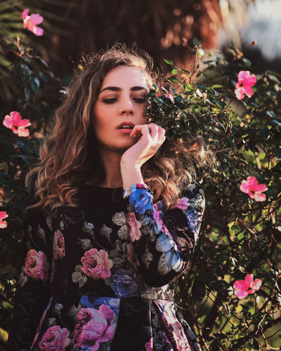 Portrait of beautiful woman with pink flower petals