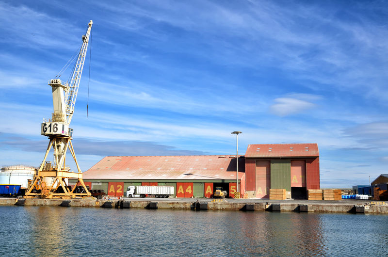 Commercial dock by pier against sky