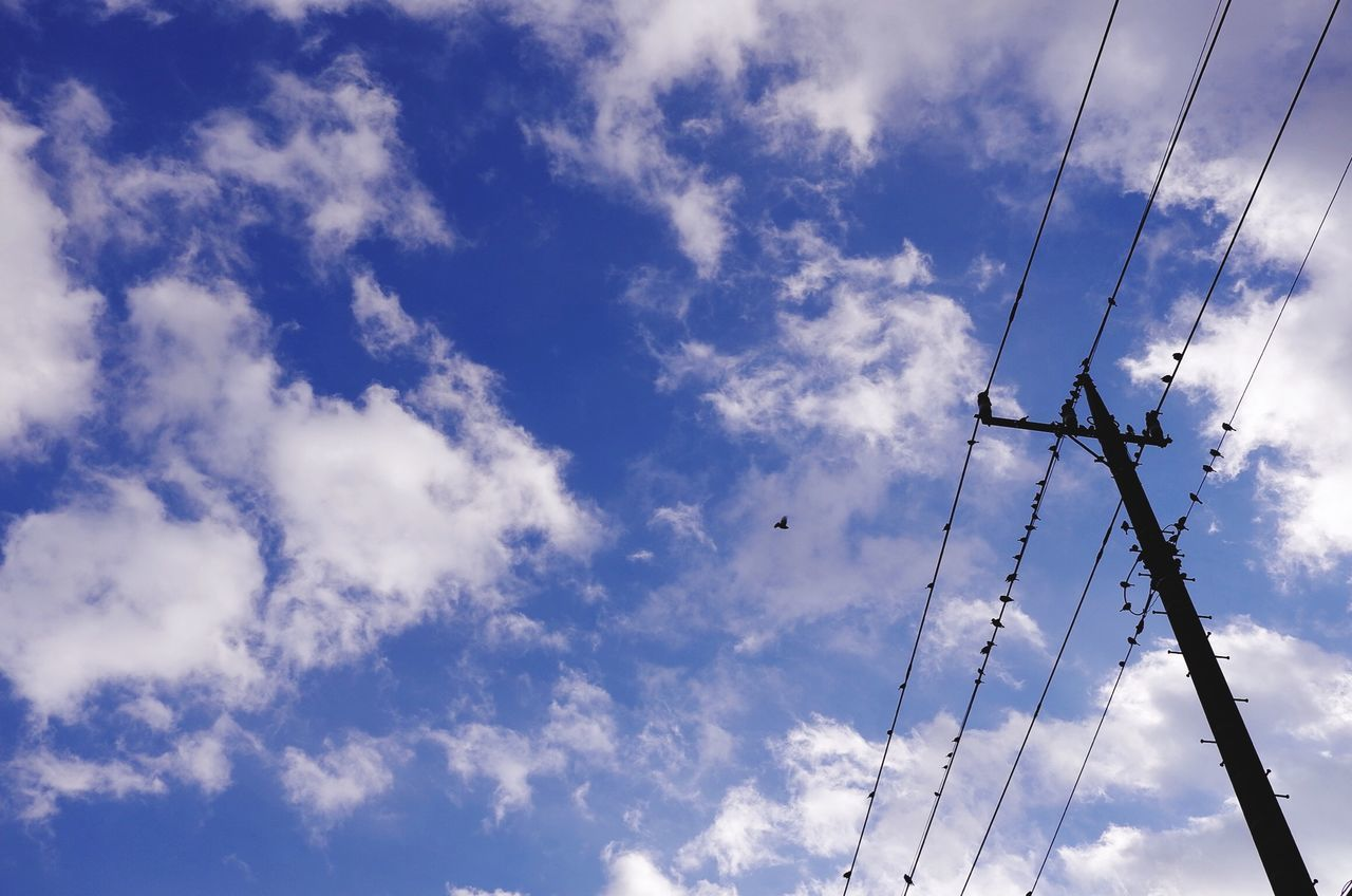 Low Angle View Of Electricity Pylons Against Blue Sky