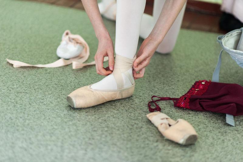 Low section of women wearing ballet shoe