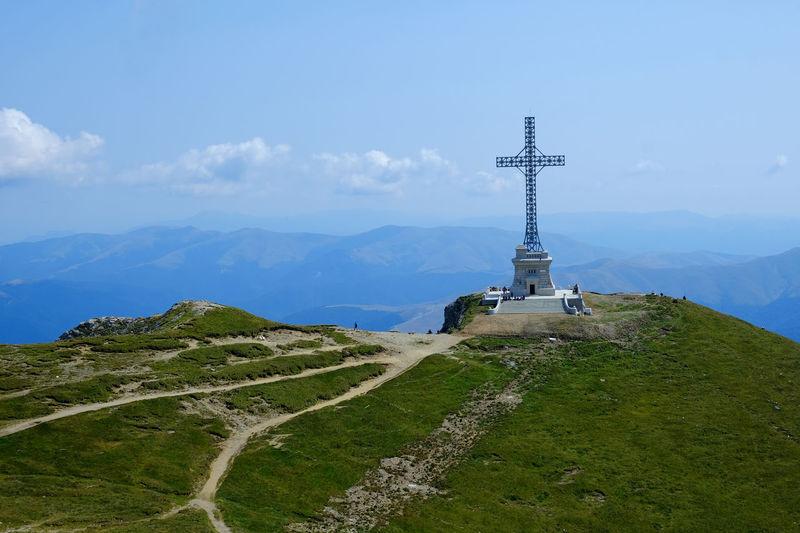 Cross on mountain against sky